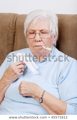 Elderly woman taking her temperature Stock photo © photography33