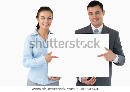 smiling businesswoman pointing at blank business card against a white background stock photo © wavebreak_media