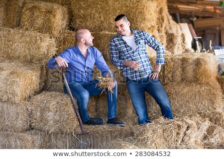 Stock photo: casual man in the grass holds a straw in his mouth