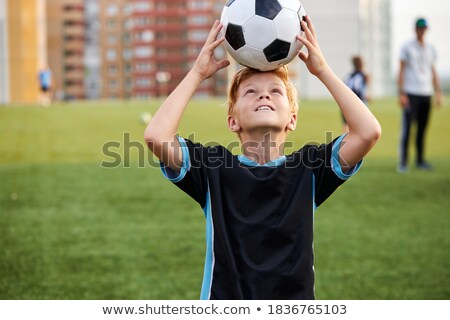 portrait of a smiling boy holding a soccer ball stock photo © imagedb