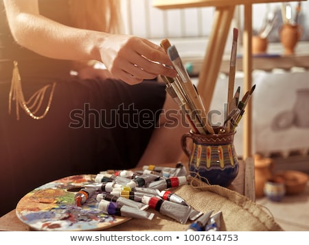 Hands of woman artist painting with paintbrush and watercolor paints  Stock photo © deandrobot