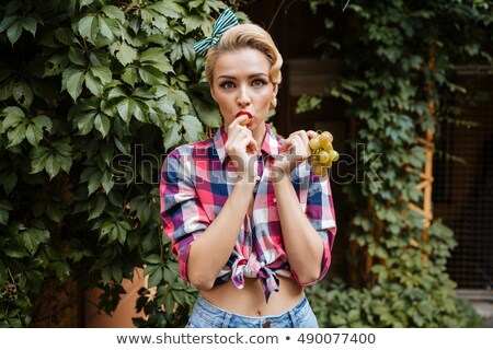 Cheerful cute pin-up girl eating grape outdoors Stock photo © deandrobot