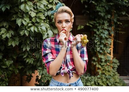 jovem · sorridente · menina · alimentação · uvas · olhando - foto stock © deandrobot