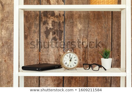 Stock photo: Stack of books on wooden table against shelf