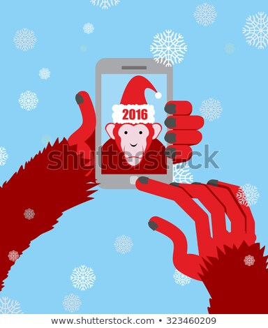 New year selfie. Monkey hooded Santa Claus makes a photo on a Sm Stock photo © popaukropa
