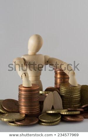 Wooden figurine sitting on heap of coins Stock photo © wavebreak_media