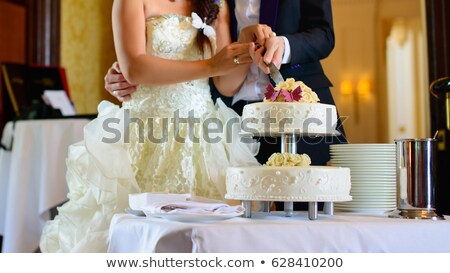 Wedding ceremony. Bride and groom cutting cake stock photo © ruslanshramko