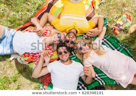 teenage girls in sunglasses on picnic blanket Stock photo © dolgachov