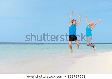 Felice Coppia sport vestiti jumping spiaggia Foto d'archivio © dolgachov