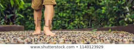 Boy Walking On A Textured Cobble Pavement, Reflexology. Pebble stones on the pavement for foot refle Stock photo © galitskaya