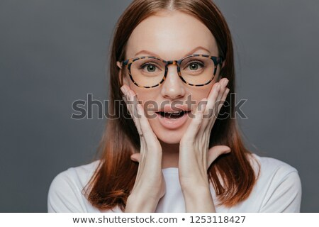 Headshot of surprised young Caucasian lady keeps both palms on her cheeks, looks with amazement, rec Stock photo © vkstudio