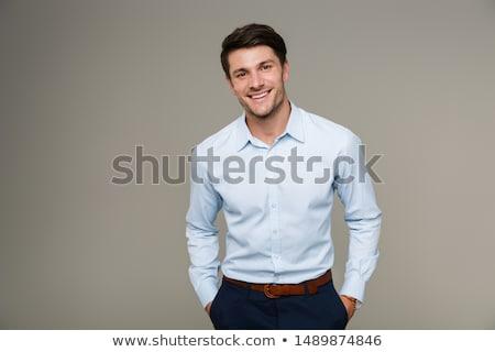 közelkép · fiatal · mosolyog · üzletember · áll · szürke - stock fotó © HASLOO