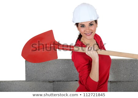 Woman stood by unfinished wall with spade Stock photo © photography33