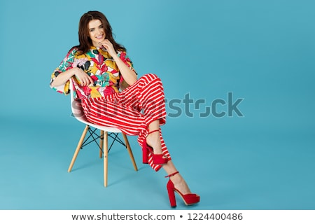 woman in bright clothes sitting in a chair stock photo © pzaxe