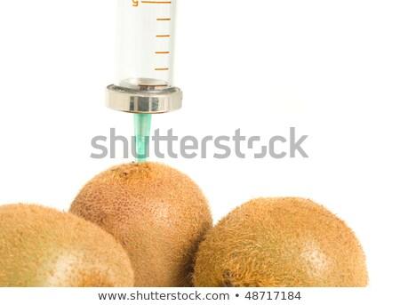 GMO - kiwi with sticked aged syringe on white Stock photo © Arsgera