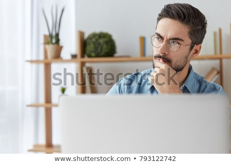 Stock photo: Portrait of a businessman looking at a laptop's screen against a white background