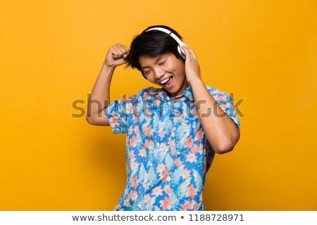 asian · man · luisteren · mp3 · hoofdtelefoon · vloer - stockfoto © szefei