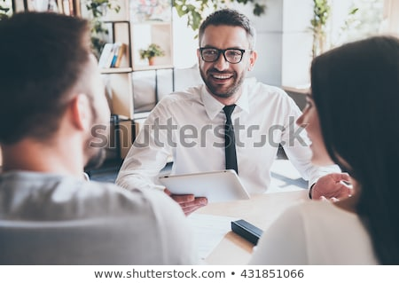 business man smiles at you with tablet in hand stock photo © feedough