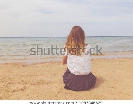 Woman on beach sitting in sand looking at ocean Stock photo © Maridav