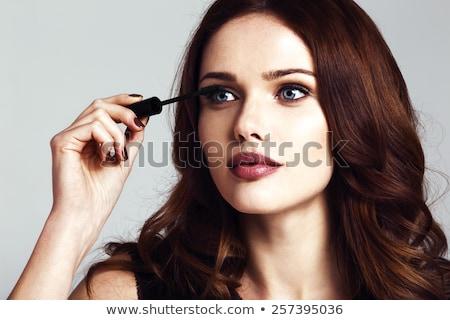 Pretty, young woman applying mascara /eyeshadows Stock photo © lightpoet