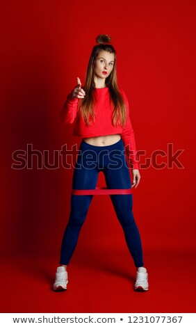 sports woman stretching leg and showing thumb up stock photo © deandrobot
