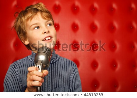 Portrait of boy with microphone on rack against red wall.  Stock photo © Paha_L