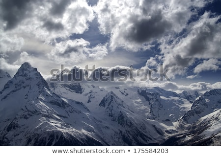 Foto stock: Sunlight Winter Mountains And Storm Clouds At Evening