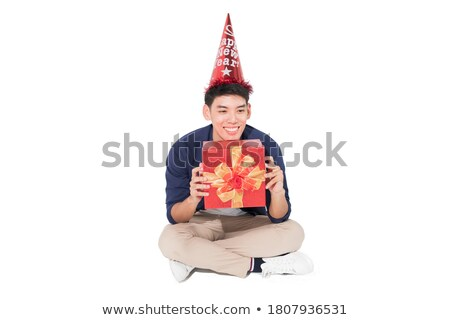 Young male sitting and holding a hat on head Stock photo © zurijeta