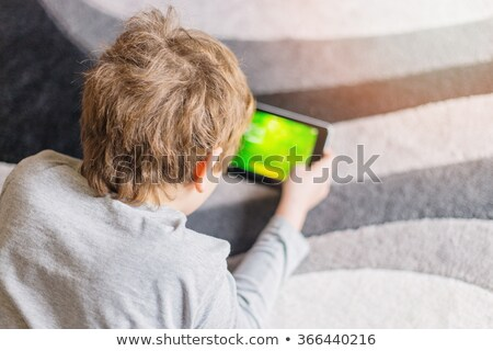 A boy using a touch screen gadget Stock photo © bluering
