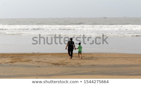 rear view of happy couple running on the beach in tropical sea p stock photo © disobeyart