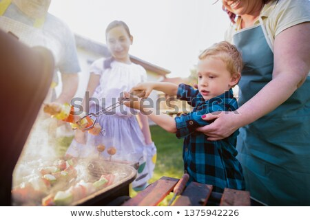 two girls and boy roasting sausages Stock photo © IS2