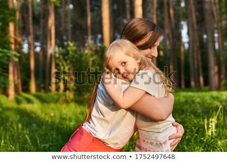 Cute loving emotional woman hugging her daughter tight while spe Stock photo © dashapetrenko