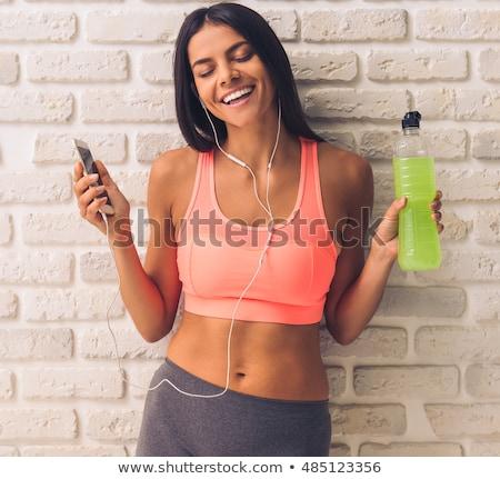mosolyog · sportos · nő · okostelefon · fülhallgató · sport - stock fotó © deandrobot