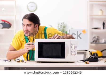 young contractor repairing oven in kitchen stock photo © elnur