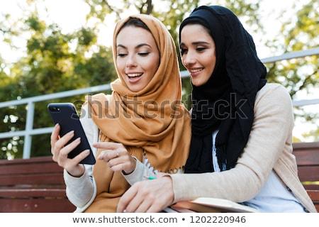 Photo of cheerful islamic women wearing headscarfs, resting in g Stock photo © deandrobot