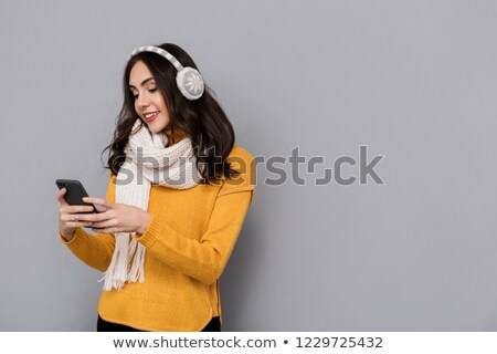 Portrait of happy woman wearing ear muffs and scarf holding mobi Stock photo © deandrobot