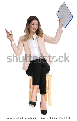 curious seated smart casual woman holds clipboard in the air stock photo © feedough