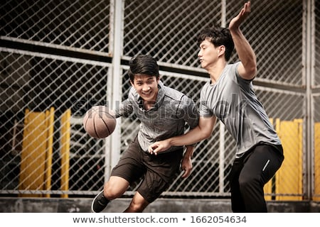 smiling young man dribbling basketball Stock photo © dolgachov