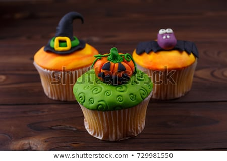 cupcake with halloween decoration on table stock photo © dolgachov