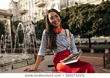 Attractive girl in sunglasses, red striped shirt holding red handbag. Stock photo © studiolucky