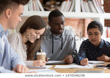 happy smiling young multiethnic friends girls doing homework using laptop outdoors in park stock photo © deandrobot