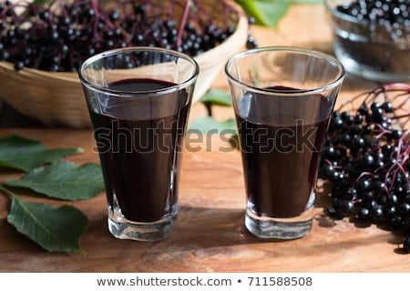 two glasses of elderberry syrup on a wooden background stock photo © madeleine_steinbach