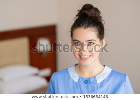 Happy brunette female in blue uniform of chamber maid standing in hotel room Stock photo © pressmaster