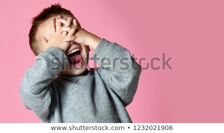 man closing his eyes by hands over grey background Stock photo © dolgachov