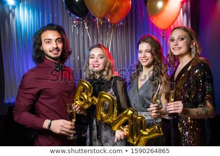 Három boldog lányok fiatalember tart fuvolák Stock fotó © pressmaster