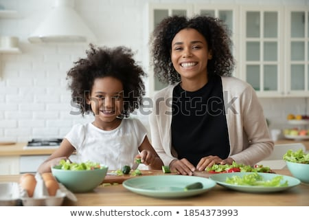 Indoor shot of caring mother with happy smile, cooks together with daughter in kitchen, prepare holi Stock photo © vkstudio