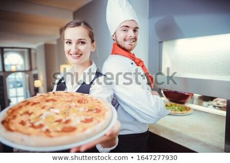 Chef cook and waitress presenting a pizza in restaurant Stock photo © Kzenon
