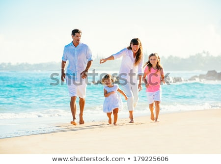 Woman having fun walking in the water on a sandy beach Stock photo © Kzenon