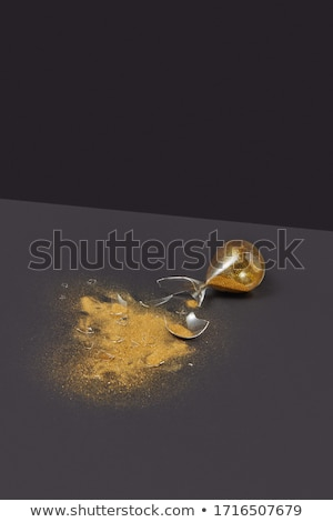 Cracked sandglass with golden sand on a dark background. Stock photo © artjazz
