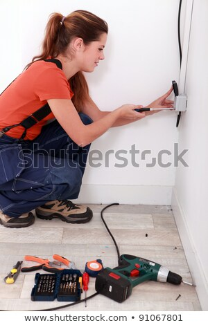 Tradeswoman fixing an electrical outlet Stock photo © photography33